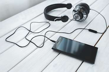 Bild på hörlurar kopplade till en mobiltelefon