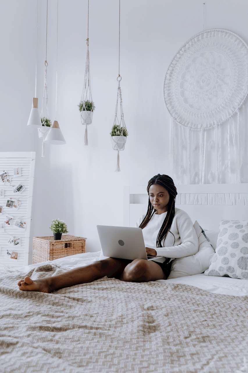Bild på en flicka som läser på en dator på sängen