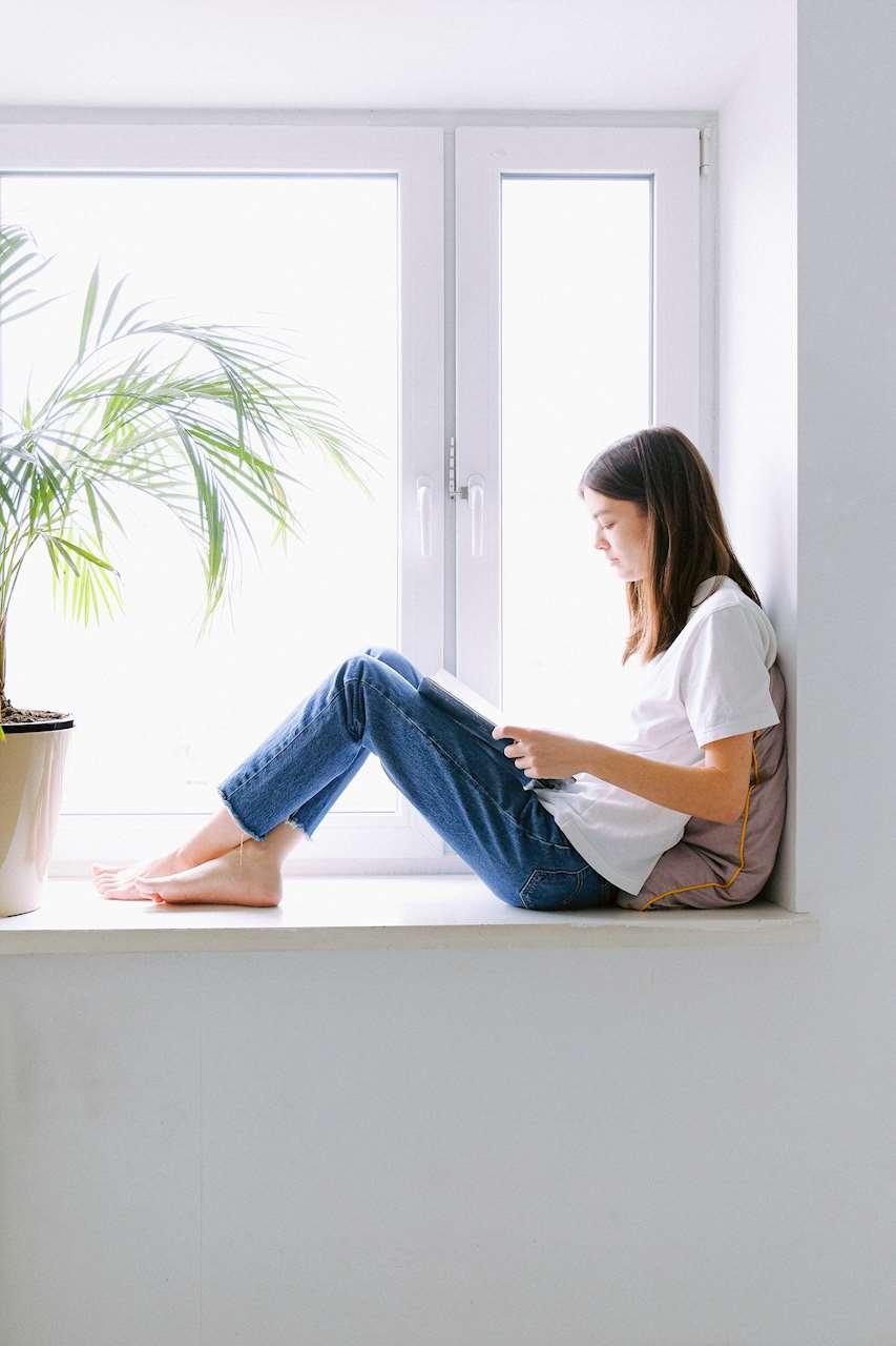 Bild på en flicka som läser vid fönstret